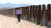 Richard Saunders, director of public safety of the Tohono O'odham Nation, walks along the vehicle barrier on the U.S. - Mexico border that crosses through the Tohono O'odham reservation in Chukut Kuk, Arizona April 6, 2017. Picture taken April 6, 2017.  REUTERS/Rick Wilking