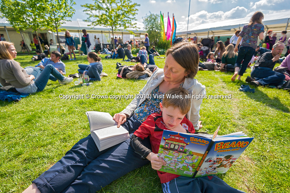 Woman and child sitting on grass reading books<br /> Hay Literary Festival 2013<br /> Hay-on-Wye<br /> Powys<br /> South<br /> Culture<br /> Arts<br /> Events