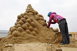 © Licensed to London News Pictures. 26/03/2013. Weston-super-Mare, UK.  A sand sculptor works on a piece from the movie Up.  The Sand Sculpture Festival at Weston-super-Mare beach.  This year's theme is Hollywood with sculptors from around the world working on film icons carved out of sand.  The festival opens to the public from 29 March.  26 March 2013..Photo credit : Simon Chapman/LNP