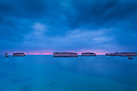 Offshore islands are backlight by a pink sunset on the horizon and surrounded by blue waters rivaling the Caribbean. Great Ocean Road, Australia.