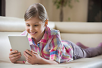 Smiling girl using tablet PC while lying on sofa at home