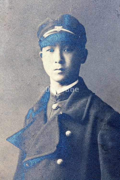 silver mirroring on a vintage portrait of a young adult boy wearing a school uniform Japan