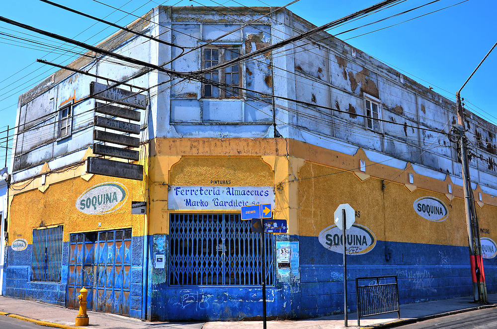 Hardware Store For Locals in Arica, Chile<br /> Despite the bright yellow and blue colors on the lower level of the facade, this building looks worn.  Most certainly the colorful product used was Soquina, a Chilean paint company.  Inside of Marko Gardilic is a hardware store most certainly aimed at the locals. This is definitely not the big box hardware store you find in the U.S.
