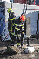 © London News Pictures. Calais, France. 04/03/16. A fireman douses a gas canister, which was removed from a burning shelter, with water to prevent it from exploding. French authorities are clearing the southern half of the Calais 'Jungle' camp, which charities estimate to contain 3,500 people. Photo credit: Rob Pinney/LNP
