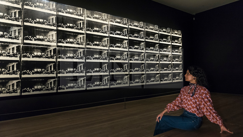 """© Licensed to London News Pictures. 10/03/2020. LONDON, UK. A staff member views """"Sixty Last Suppers"""", 1986, by Andy Warhol, which has never been seen in the UK before. Preview of """"Andy Warhol"""", a retrospective of over 100 works by one of the most recognisable artists of the late 20th century.  The exhibition runs 12 March to 6 September 2020 at Tate Modern.  Photo credit: Stephen Chung/LNP"""