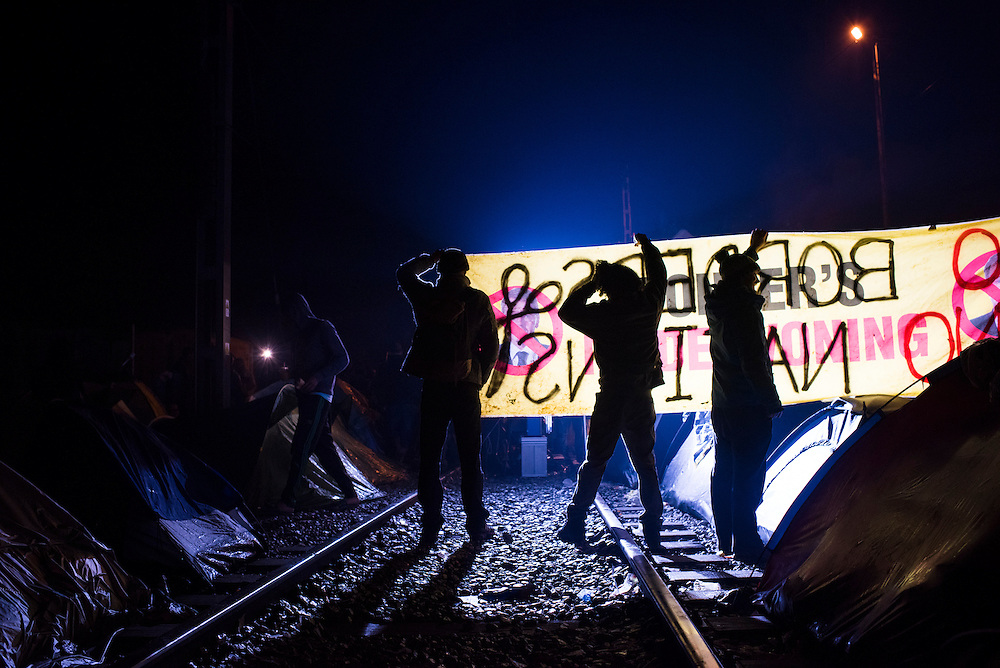 Refugees hold up signs imploring authorities to open the border on railroad tracks leading to the Macedonian (FYROM) border on March 7, 2016 in Idomeni, Greece.