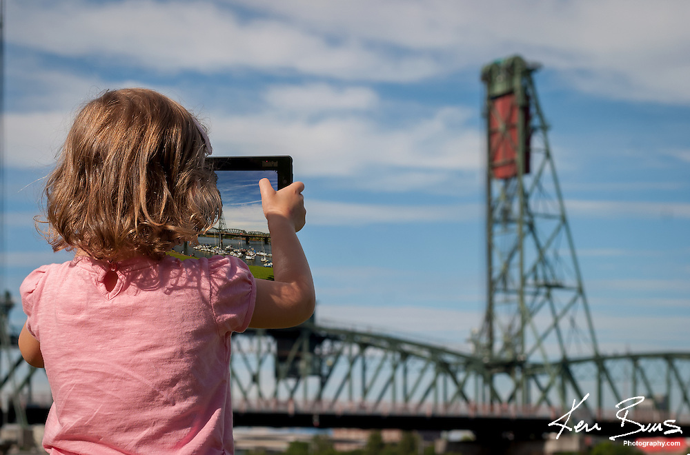 A young girl standing besides the Willamette river in Portland Oregon, using a tablet to take a photograph of the Hawthorne Bridge, on a sunny day