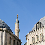 Domes of a mosque in Istanbul, with a minaret peaking up from between them against a clear blue sky.