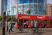A tour bus drives beneath a large advert for American Airlines of a wide-bodied airliner in Waterloo, south London.