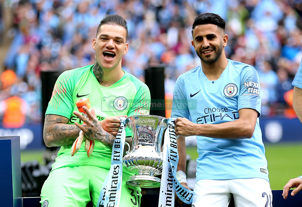 Manchester City goalkeeper Ederson (left) and Riyad Mahrez celebrate with the trophy at the end of the match