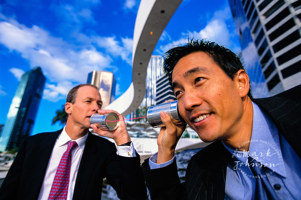 Brisbane, Australia --- Businessmen Playing with Tin Can Phone