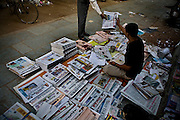 Newspaper sellers sort out and sell newspapers on the road in the Mehar Chand market street early in the morning on 20th October 2008 in New Delhi, India. With internet still out of reach for 95% of the country and literacy higher than ever, more and more are turning to newspapers and magazines.  Photo : Suzanne Lee