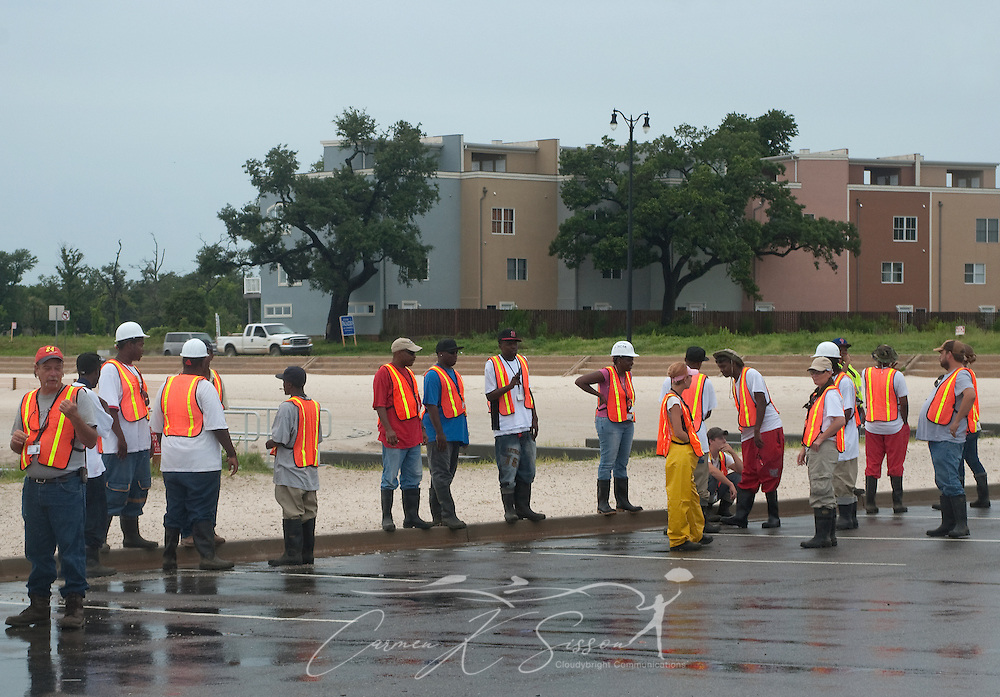 Oil spill cleanup workers await instruction on the beach in Gulfport, Miss. June 30, 2010. Mississippi had been largely spared from the effects of the Deepwater Horizon oil rig explosion April 20, 2010, but winds from Hurricane Alex began pushing oil ashore earlier this week, affecting beaches from Biloxi to Pass Christian.(Photo by Carmen K. Sisson/Cloudybright)