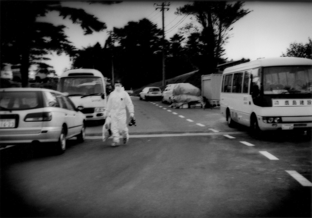 Nuclear power plant worker, wearing his protective white suite and carrying a respirator mask, walks toward the buses in the off-limits J Village that will ferry him to the stricken Fukushima Daiichi Nuclear Power Plant to help in the dangerous task of to bringing several of the reactors under control.  Hironomachi, Fukushima Prefecture, Japan.  J Village was originally built as a training camp to prepare a new generation of young Japanese for the national football (soccer) team.
