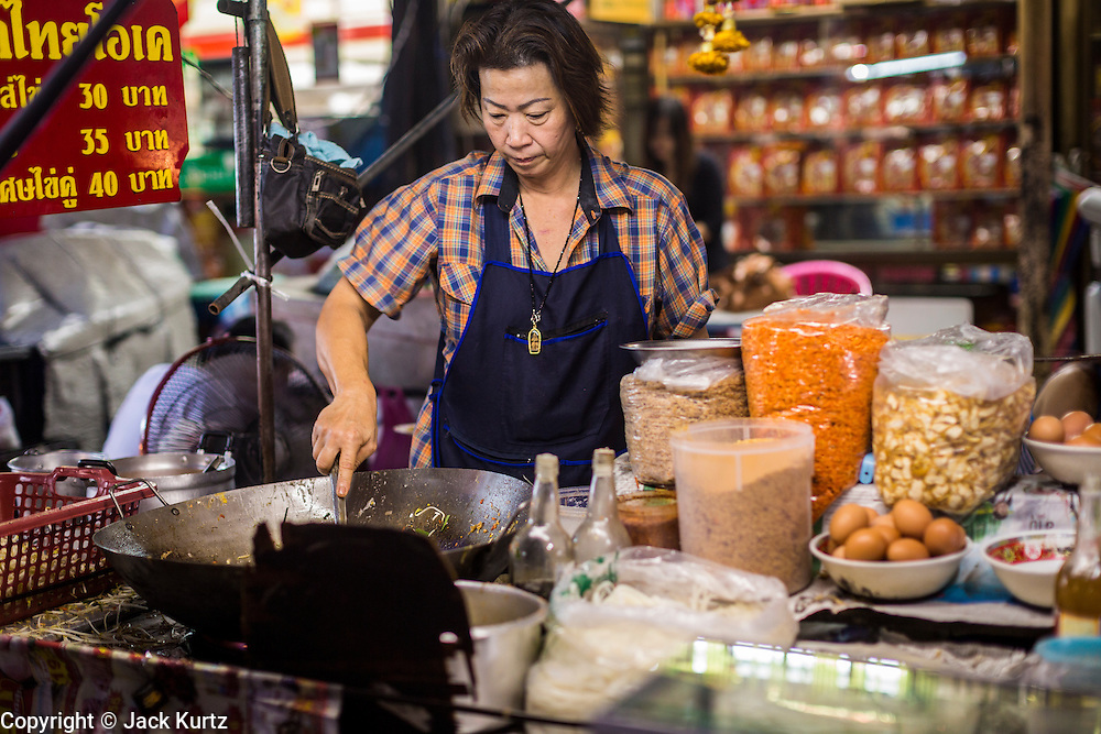 18 SEPTEMBER 2013 - BANGKOK, THAILAND: A vendor makes stir fried dishes in her cart in the Chinatown section of Bangkok. Thailand in general, and Bangkok in particular, has a vibrant tradition of street food and eating on the run. In recent years, Bangkok's street food has become something of an international landmark and is being written about in glossy travel magazines and in the pages of the New York Times.      PHOTO BY JACK KURTZ