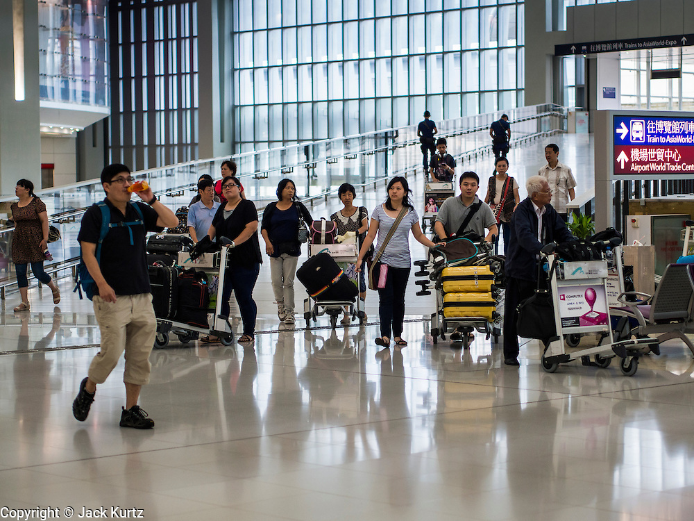 14 AUGUST 2013 - HONG KONG:  Passengers walk into Terminal 1 at Hong Kong International Airport. Dozens of flights were delayed at one of the busiest airports in Asia and Hong Kong raised their alert to level 8, the highest, and closed schools and many businesses because of Severe Typhoon Utor. The storm passed within 260 kilometers of Hong Kong before making landfall in mainland China. Severe Typhoon Utor (known in the Philippines as Typhoon Labuyo) is an active tropical cyclone located over the South China Sea. The eleventh named storm and second typhoon of the 2013 typhoon season, Utor formed from a tropical depression on August 8. The depression was upgraded to Tropical Storm Utor the following day, and to typhoon intensity just a few hours afterwards. The Philippines, which bore the brunt of the storm, reported 1 dead in a mudslide and 23 fishermen missing at sea.  PHOTO BY JACK KURTZ