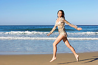 Young woman running on beach side view