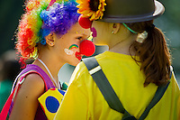 "Cali Miller, left, and Brooke McClurkin prepare to march through the Art on the Green area Friday with the rest of their clowning class from the Citizen's Council for the Arts ""ArtShop"" program."