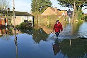 © Licensed to London News Pictures. 12/01/2014. Wraysbury, UK. People walk past flooded properties. Flooding in Wraysbury, Berkshire today 12th January 2014.  Flooding and property damage is expected to continue along the River Thames.  Large areas of Britain are experiencing flooding after wet weather. Photo credit : Stephen Simpson/LNP