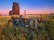 Grain elevator with old tractor at dawn<br /> Bents<br /> Saskatchewan<br /> Canada