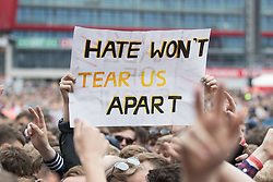 "© Licensed to London News Pictures . 27/05/2017 . Manchester , UK . A woman holds up a sign reading ""Hate won't tear us apart "" . Fans inside the stadium . Manchester music line up , featuring Courteeners , Charlatans , Blossoms and Cabbage , at the Emirates Old Trafford Stadium . Photo credit : Joel Goodman/LNP"