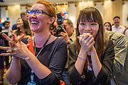 07 NOVEMBER 2012 - BANGKOK, THAILAND:  MARY CONGER and NITHIDA LEEDHIRAKUL watch as US election results are posted at the US Embassy's election watch party in Bangkok. They all supported President Obama's reelection. US President Barack Obama won a second term Tuesday when he defeated Republican Mitt Romney. Preliminary tallies gave the President more than 300 electoral votes, well over the 270 needed to win. The election in the United States was closely watched in Thailand, which historically has very close ties with the United States. The American Embassy in Bangkok sponsored an election watching event which drew thousands to a downtown Bangkok hotel. American Democrats in Bangkok had their own election watch party at a restaurant in Bangkok.      PHOTO BY JACK KURTZ