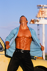 man with an open shirt exposing his very muscular and oiled up body outdoors