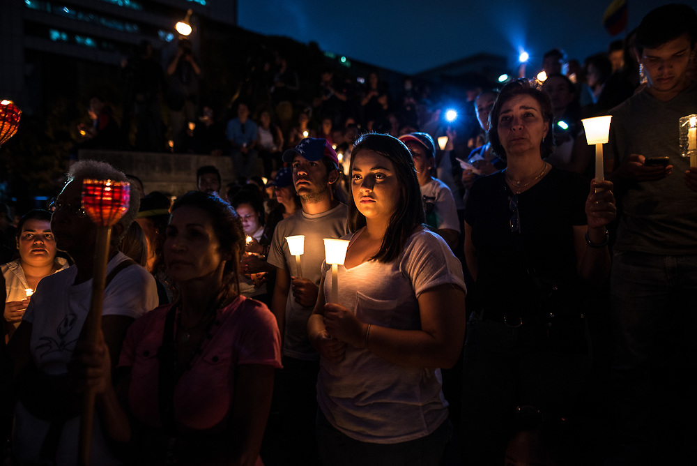 """CARACAS, VENEZUELA - MAY 17, 2017: Lucia Gonzalo, 22, holds a candle at a vigil for fallen anti-government protesters. """"I don't know the Venezuela that my parents talk about, because I've never known freedom,"""" she said. """"We will not leave the streets until this [government] is over."""" The streets of Caracas and other cities across Venezuela have been filled with tens of thousands of demonstrators for nearly 100 days of massive protests, held since April 1st. Protesters are enraged at the government for becoming an increasingly repressive, authoritarian regime that has delayed elections, used armed government loyalist to threaten dissidents, called for the Constitution to be re-written to favor them, jailed and tortured protesters and members of the political opposition, and whose corruption and failed economic policy has caused the current economic crisis that has led to widespread food and medicine shortages across the country.  Independent local media report nearly 100 people have been killed during protests and protest-related riots and looting.  The government currently only officially reports 75 deaths.  Over 2,000 people have been injured, and over 3,000 protesters have been detained by authorities.  PHOTO: Meridith Kohut"""