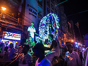"22 OCTOBER 2015 - YANGON, MYANMAR: Hindus participate in an evening procession to honor the goddess Durga on the last day of Navratri in Yangon. Navratri, literally ""nine nights"" is a Hindu festival devoted to the Goddess Durga. Navratri festival combines ritualistic puja (prayer) and fasting. Navratri in India follows the lunar calendar and is celebrated in September/October as Sharad Navratri. It's widely celebrated in countries in Southeast Asia that have large Hindu communities, including Myanmar (Burma). Many of Myanmar's Hindus are descendants of Indian civil servants and laborers who came to Myanmar when it was the British colony of Burma.   PHOTO BY JACK KURTZ"
