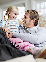 Girl (3-4) sitting in father's lap in house