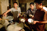 Artists are have gathered around a big noodle pot after the show. They have a cook that prepare the food for them. Because they don't have much money they rarely eat meat.