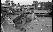 """Flooding at the Dodder..1986..26.08.1986..08.26.1986..28th August 1986..As a result of Hurricane Charly (Charlie) heavy overnight rainfall was the cause of severe flooding in the Donnybrook/Ballsbridge areas of Dublin. In a period of just 12 hours it was stated that 8 inches of rain had fallen. The Dodder,long regarded as a """"Flashy"""" river, burst its banks and caused great hardship to families in the 300 or so homes which were flooded. Council workers and the Fire Brigades did their best to try and alleviate some of the problems by removing debris and pumping out some of the homes affected..Note: """"Flashy"""" is a term given to a river which is prone to flooding as a result of heavy or sustained rainfall...Picture shows work men at the site where the road had subsided near the bridge over the Dodder at Ballsbridge, Dublin.The picture also shows damage to a water main."""