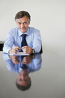 Business man sitting at conference table portrait