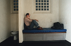 Man sitting on bench in prison cell,