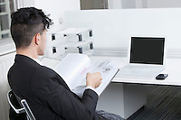 Rear view of young businessman working at office
