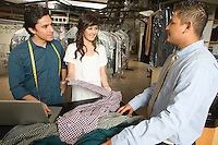 Man and woman serving a customer in the laundrette
