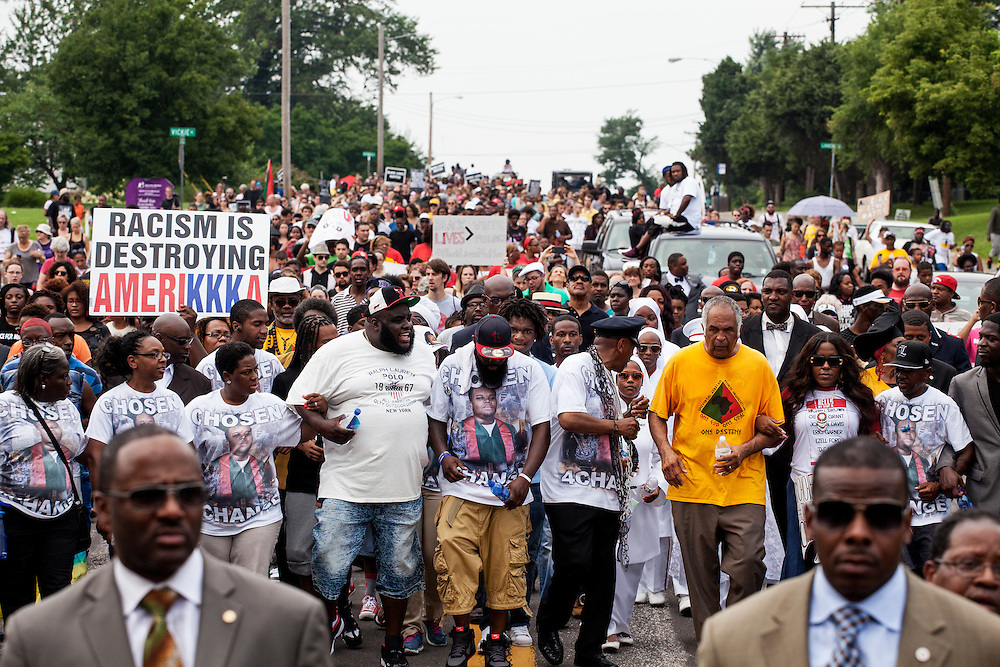 Hundreds of demonstrators, including the Brown family, take part in a march from the Canfield memorial to St. Mark's Church in Ferguson. Protesters took to the streets to commemorate the one year anniversary of the death of Michael Brown Jr. in Ferguson.