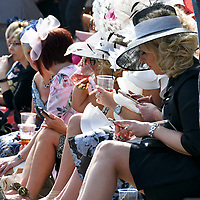 National Hunt Horse Racing - 2019 Randox Health Grand National Festival - Saturday, Day Three (Grand National Day)<br /> <br /> female racegoers sit in the sunshine before  the 1.45 Gaskells Handicap Hurdle (Grade 3) (Class 1)<br /> at Aintree Racecourse.<br /> <br /> COLORSPORT/WINSTON BYNORTH