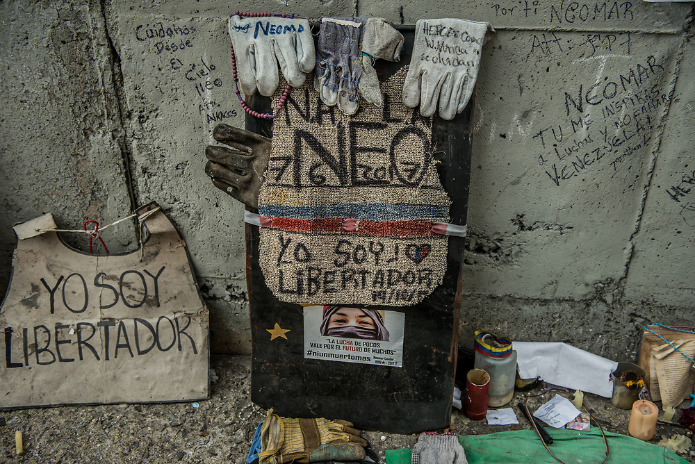 CARACAS, VENEZUELA - JULY 27, 2017:  Neighbors take a break from blocking the street,  to pay tribute to Neomar Lander, who was killed in this spot during an anti-government protest.   Neighbors blocked their streets, in support of a national strike, called by the political opposition to last for  48 hours, all day July 26th and 27th. They called for their supporters to close businesses, not go to work, and instead create barricades to block off their streets.  Opposition controlled areas of the country were completely shut down.  The strike was called as part of the opposition's civil resistance movement - that began on April 1st, to protest against the Socialist government's attempt to elect a new constituent assembly that will have the power to re-write the constitution, and will threaten democracy.  PHOTO: Meridith Kohut for The New York Times