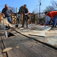 Thomas Wells | BUY at PHOTOS.DJOURNAL.COM<br /> Kevin Galloway, from left, Dalton Suggs and Shelton Tutor remove all the old flooring in order to get down to the orginal hard wood floors so they continue the disassembly of a home that was once lived in by Elvis Presley.