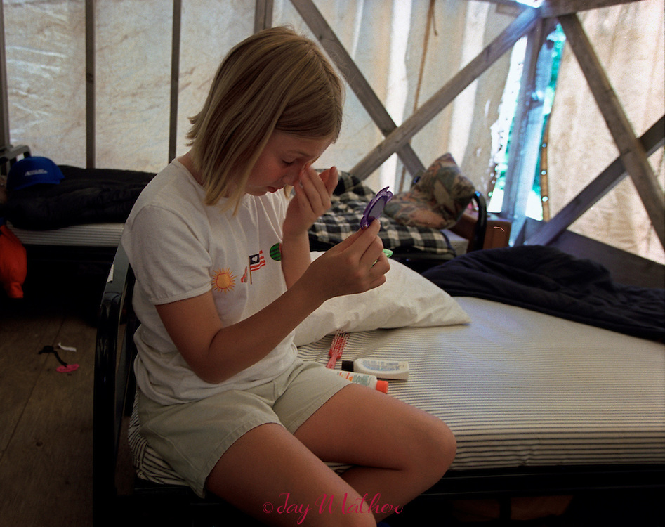 A camp applies sunscreen in her tent at Camp Menzies.  July 3, 2000.