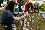 12 SEPTEMBER 2003 - CANCUN, QUINTANA ROO, MEXICO: Mourners light candles and place flowers at the spot Lee Kyung-hae, a Korean anti-globalization protestor committed suicide Wednesday during an anti-globalization protest in Cancun, Mexico. A shrine honoring Kyung-hae has been built at the spot where he died. Thousands of anti-globalization protestors have come to Cancun to try to disrupt the 5th Ministerial meeting of the World Trade Organization. The protestors have been restricted to downtown Cancun, while the WTO is meeting 10 miles away in the Cancun tourist zone. PHOTO BY JACK KURTZ