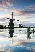 Group of authentic windmills reflection in polder dyke early morning at Kinderdijk UNESCO World Heritage Site, Holland