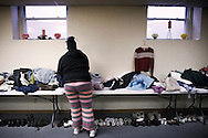"OHIO, Toledo, October 27, 2012:  A girl is seen as she is choosing used clothes inside the basement of the  ""Primera Iglesia Bautista"" where clothes and food are distributed. ALESSIO ROMENZI"