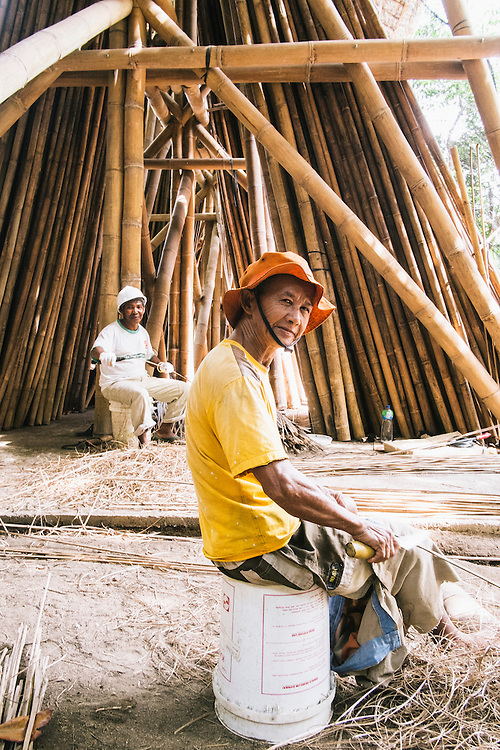 Workers prepare bamboo building materials