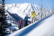 Three women friends ski touring in the Wasatch Mountain backcountry above Alta, Utah.