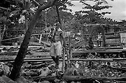 A man carrying a small child walks through a settlement of displaced famies assembled on wetland. <br /> Turbo, Antioquia. Sep 1997.