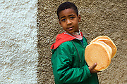 A Moroccan boy collect some unleavened bread for his mother, Meknes, Morocco