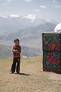 A girl outside the yurt where she lives with her family in summer on the high alltitude jailoo (pasture) in the Baybiche-Too range of the Tien Shan mountains in Kyrgyzstan