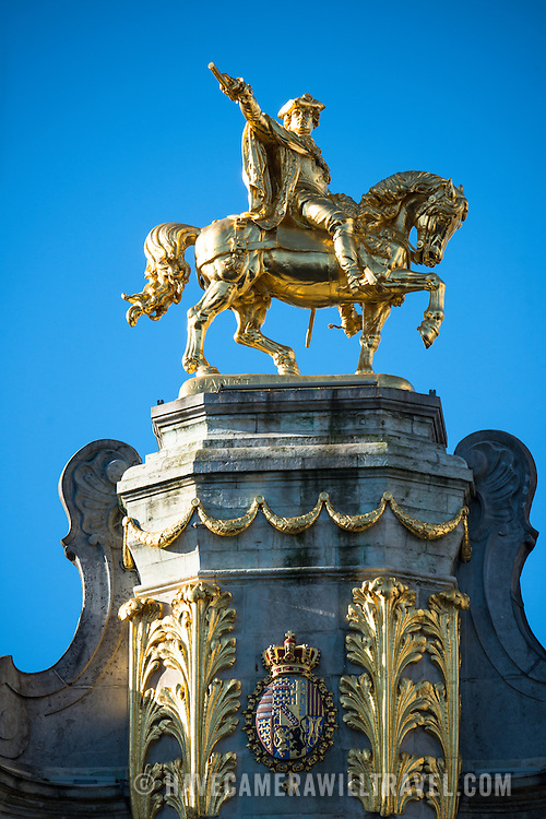 A gold equestrian statue sits astride one of the ornate buildings on Grand Place (La Grand-Place), a UNESCO World Heritage Site in central Brussels, Belgium. Lined with ornate, historic buildings, the cobblestone square is the primary tourist attraction in Brussels.